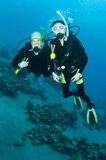 Man and woman scuba dive togeather. Romantic couple scuba dive together in the ocean on a coral reef royalty free stock image