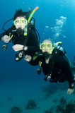 Man and woman scuba dive togeather. Romantic couple scuba dive together in the ocean on a coral reef royalty free stock photo