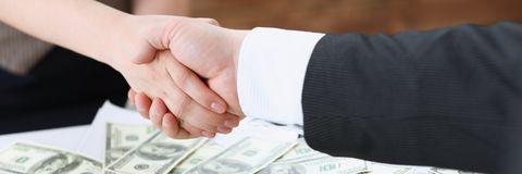 Man and woman shake hands over stack Royalty Free Stock Photo