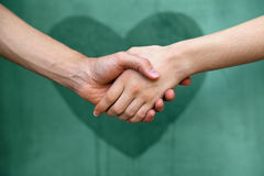 Man and woman shaking hands. With a heart painted wall in background stock photos