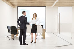 Man and woman shaking hands in board room with square window. Man and women shaking hands in conference room with large square window; glass wall and a table Royalty Free Stock Photo