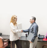 Man and woman shaking hands in office. Man and women meeting in office shaking hands royalty free stock images