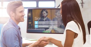 Man and woman shaking hands with sign up page on monitor in background. Digital composite of Man and women shaking hands with sign up page on monitor in Royalty Free Stock Photos