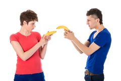 Man and woman shooting each other with bananas. Man and women shooting each other with bananas isolated on white Stock Images