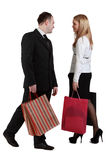Man and woman shopping. Image of a women and a men with shopping bags passing by themselves and looking to each other face Stock Image