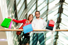 Man and woman in shopping mall with bags. Couple - man and woman - in a shopping mall with colorful bags looking at their bought stuff Stock Photos