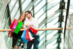 Man and woman in shopping mall with bags. Couple - man and woman - in a shopping mall with colorful bags looking at their bought stuff Stock Photo