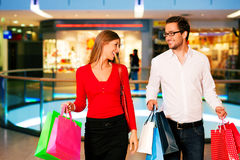 Man and woman in shopping mall with bags. Couple - man and woman - in a shopping mall with colorful bags simply having fun royalty free stock photo