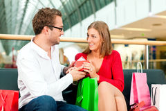 Man and woman in shopping mall with bags Royalty Free Stock Photos