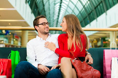 Man and woman in shopping mall with bags. Couple - man and woman - in a shopping mall with colorful bags; they having a break Royalty Free Stock Images