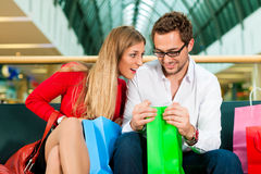 Man and woman in shopping mall with bags. Couple - man and woman - in a shopping mall with colorful bags, they are checking what exactly they do have bought, she Stock Photography