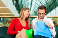 Man and woman in shopping mall with bags Stock Image