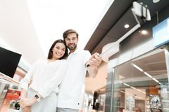 Man and woman in shopping mall. Couple is taking selfie with selfie stick. Man and women in shopping mall. Couple is taking selfie with selfie stick. Couple is royalty free stock photography