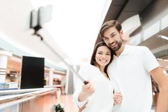 Man and woman in shopping mall. Couple is taking selfie with selfie stick. royalty free stock images