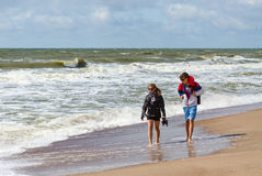 Man and woman are on shore of beach on Baltic Sea in sunny windy Stock Photo