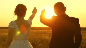A man and a woman show a heart with their hands at the sunset of the golden sun. Lovers on a romantic trip. Teamwork of stock footage
