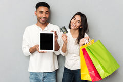 Man and woman showing credit card and tablet with empty screen Royalty Free Stock Images