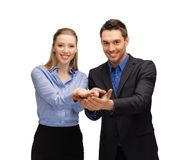 Man and woman showing something on the palms Royalty Free Stock Image