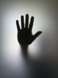 Man or woman showing stop gesture hand silhouette through frosted glass Royalty Free Stock Photo