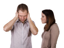 The man and the woman. Man shutting his ears and not listening to the persistent yelling of his spouse Royalty Free Stock Photo