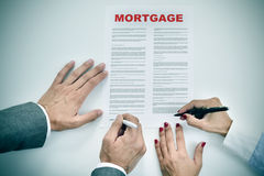 Man and woman signing a mortgage loan contract. High-angle shot of a man and a woman signing a mortgage loan contract Stock Photo