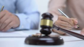 Man and woman signing prenuptial agreement, gavel with engagement rings on table. Stock footage stock footage