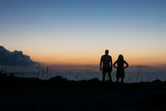 A man and a woman in silhouette looking towards the horizon at the setting sun over the Mediterranean Royalty Free Stock Photos