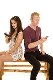 Man woman sit back to back phones surprised Stock Photography