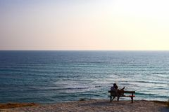 Couple lovers on bench look at blue sea. Sihlouette stock photos