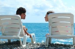 Man and woman sit in deckchair. Young man and woman sit in deckchair on beach Royalty Free Stock Images