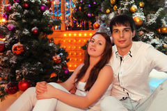 Man and woman sit near christmas trees Stock Photos