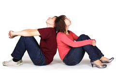 Man and woman sitting back to back Stock Images