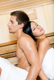 Man and woman sitting back to back in sauna Royalty Free Stock Photos