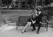 Man and woman sitting  on a bench Stock Images