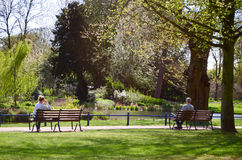 Man and woman sitting on benches. A man and a woman sitting on benches in a park. Great for articles on health benefits and relaxation Royalty Free Stock Images