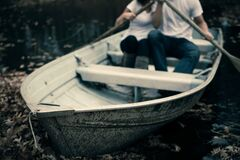 Man and Woman Sitting on Boat Holding Paddles Royalty Free Stock Photography