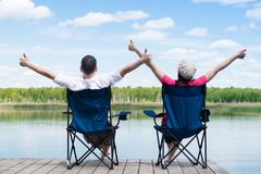 Man and woman are sitting on chairs and enjoying the beautiful nature of the lake royalty free stock image