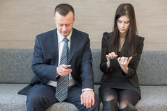 Man and woman sitting with communication device Royalty Free Stock Images