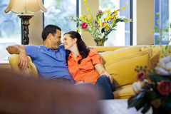 Man and woman sitting on couch. Royalty Free Stock Images