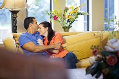Man and woman sitting on couch. Stock Photo