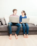 Man and woman sitting on couch with laptops and looking at each other Stock Photo