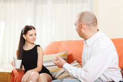 Man and woman sitting on couch and talking stock photography