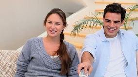Man and woman sitting on the couch watching TV. While laughing as using the tv remote stock footage