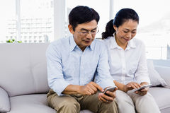 Man and woman sitting on couch Stock Photography