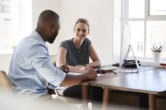 Man and woman sitting at a desk talking in an office smiling. Man and women sitting at a desk talking in an office smiling Stock Photo