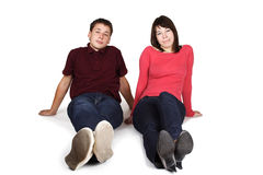 Man and woman sitting on floor, front view Royalty Free Stock Photo