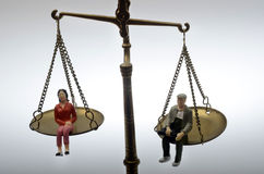 Man and woman sitting on golden weighing scale Royalty Free Stock Photo