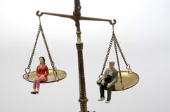 Man and woman sitting on golden weighing scale Royalty Free Stock Images
