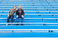 Man and woman sitting on grandstand Royalty Free Stock Photo