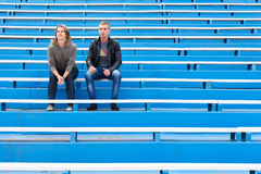 Man and woman sitting on grandstand Stock Photo
